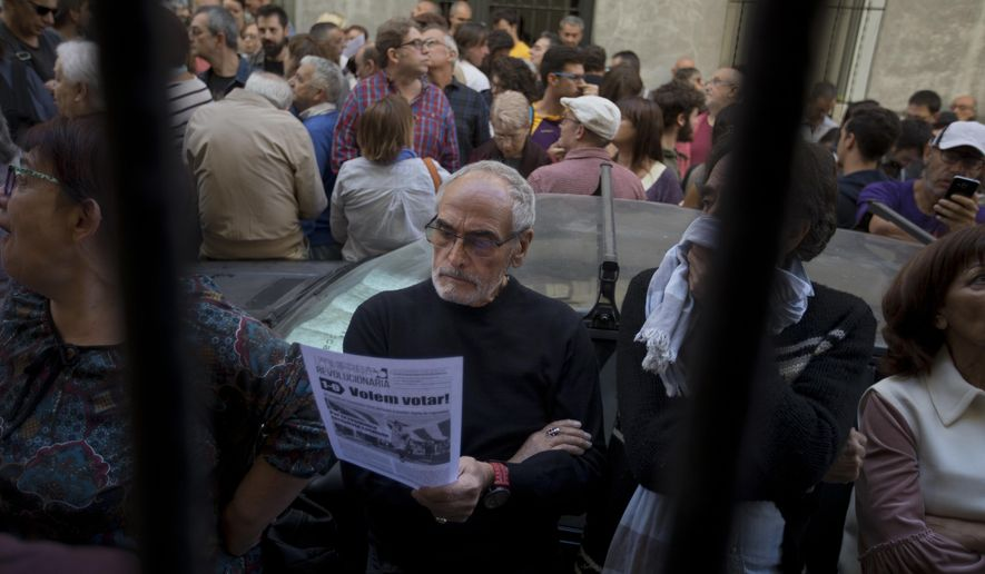 A man stands in the street reading a pamphlet urging people to vote during an event to support the Catalonia independence referendum in Madrid, Spain, Sunday, Sept. 17, 2017. Political tensions in Spain are increasing as the proposed voting date of Oct. 1 nears. The Catalan government has been scrambling to push forward the vote, despite the central government's warnings that local municipalities are not allowed to use public buildings for it and mayors can be legally prosecuted for it. (AP Photo/Paul White)
