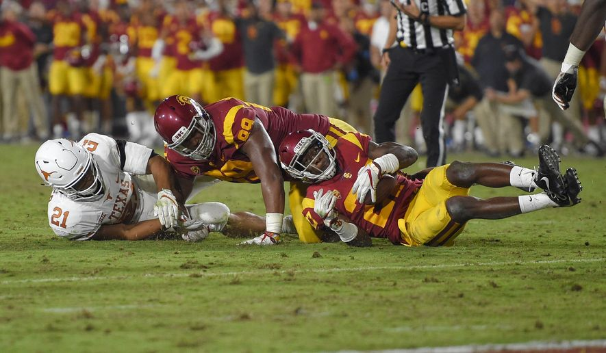 Southern California cornerback Ajene Harris, right, recovers a fumble by Texas as Texas running back Kyle Porter, left, and defensive lineman Christian Rector fall during the second overtime of an NCAA college football game, Saturday, Sept. 16, 2017, in Los Angeles. USC won 27-24 in two overtimes. (AP Photo/Mark J. Terrill)