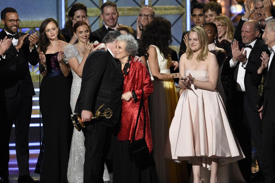 """Bruce Miller, from left, Margaret Atwood, and Elisabeth Moss accept the award for outstanding drama series for """"The Handmaid's Tale"""" at the 69th Primetime Emmy Awards on Sunday, Sept. 17, 2017, at the Microsoft Theater in Los Angeles. (Photo by Chris Pizzello/Invision/AP) ** FILE **"""