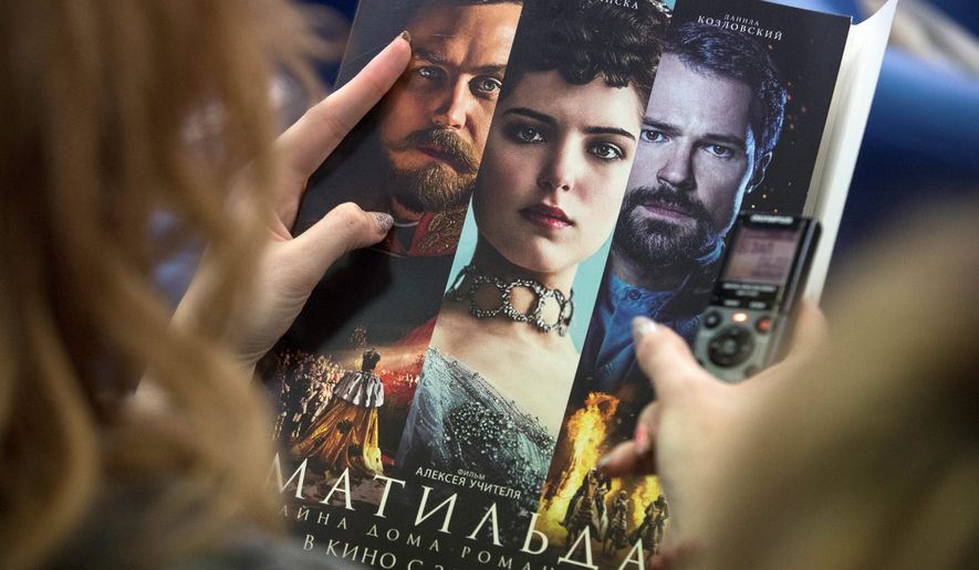 """A woman holds an official poster of """"Matilda,"""" a film focusing on on Czar Nicholas II's romantic affair with ballet dancer Matilda Kshesinskaya. The film has aroused controversy in Russia. (Associated Press/File)"""
