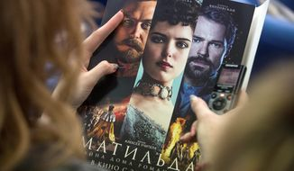 "A woman holds an official poster of ""Matilda,"" a film focusing on on Czar Nicholas II's romantic affair with ballet dancer Matilda Kshesinskaya. The film has aroused controversy in Russia. (Associated Press/File)"