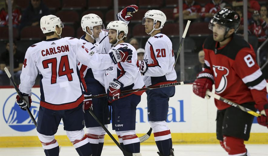 As New Jersey Devils defenseman Will Butcher (8) skate past, Washington Capitals players defensemen John Carlson, left, and Christian Djoos, of Sweden, second left, center Lars Eller (20), of Denmark, celebrate a goal by left wing Nathan Walker, third right, during the first period of a preseason NHL hockey game, Monday, Sept. 18, 2017, in Newark, N.J. (AP Photo/Mel Evans)
