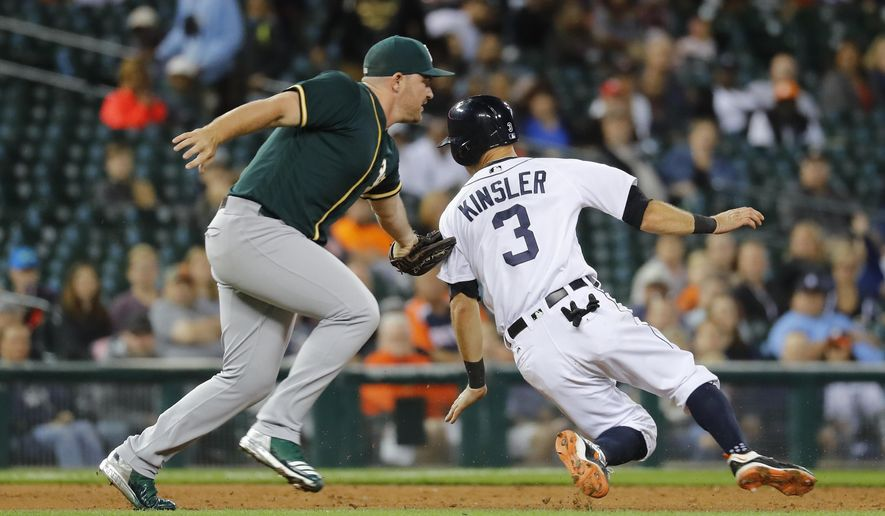 Oakland Athletics relief pitcher Liam Hendriks, left, tags Detroit Tigers' Ian Kinsler (3) out at third base in a rundown in the fifth inning of a baseball game in Detroit, Monday, Sept. 18, 2017. (AP Photo/Paul Sancya)