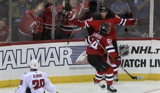 As Washington Capitals Christian Djoos, of Sweden, (20), skates past, New Jersey Devils right wing Stefan Noesen (23) celebrates his goal with center Joseph Blandisi (64) during the second period of an NHL preseason hockey game, Monday, Sept. 18, 2017, in Newark, N.J. (AP Photo/Mel Evans)
