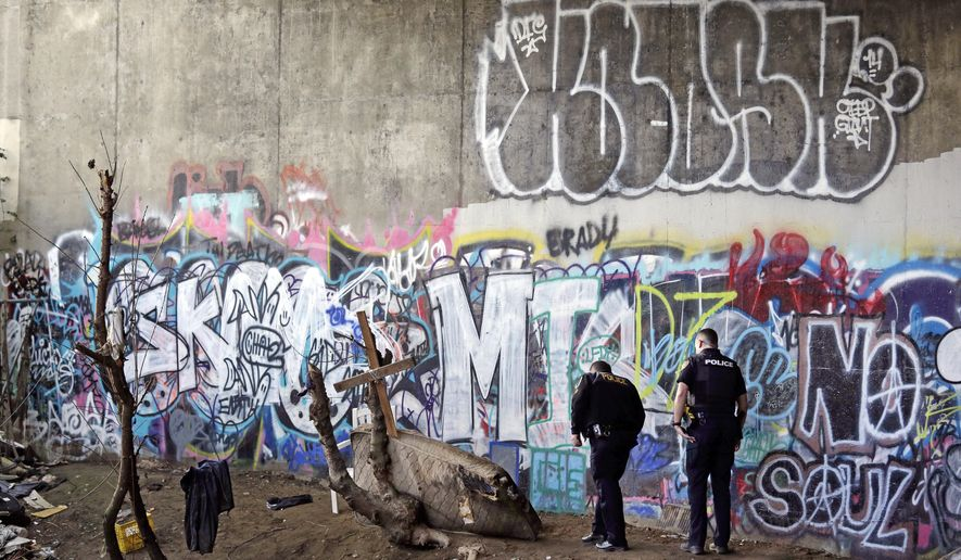 FILE - In this Feb. 16, 2017 file photo, police Sgt. Mike Braley, left, and officer Kevin Davis walk along the bottom of a highway overpass, a known location for drug use, to check for anyone living there in Everett, Wash., as overdose deaths from opioids and heroin spiked in the city. Opening statements are set to begin Monday afternoon, Sept. 18, 2017, in a lawsuit by the city of Everett against the makers of the prescription opioid OxyContin, in which it claims the pharmaceutical company knew its prescription painkiller was being funneled into the black market, helping create the opioid epidemic. (AP Photo/Elaine Thompson, File)