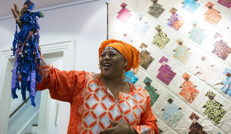 """In this Tuesday, Sept. 5, 2017, photo, Karen """"Queen Nur"""" Abdul-Malik displays a doll inside the """"Dolls of Distinction"""" exhibition at the Smithville Mansion in Eastampton, N.J. Abdul-Malik has been telling stories since she was 9-years-old. The Willingboro resident travels the country and the world, making stops at storytelling appearances and events. Abdul-Malik continues to preserve African American culture through her folk telling efforts. (Joe Lamberti/Camden Courier-Post via AP)"""