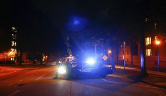 Police block off streets in front of a police station at Georgia Tech where protests happened earlier and at least one police car was burned on Monday, Sept. 18, 2017, in Atlanta. Protesters were demonstrating against the shooting, which resulted in a fatality, of a student on Saturday. (AP Photo/Kevin D. Liles)