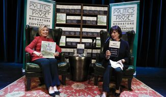 """Hillary Clinton holds her book """"It Takes A Village"""" as she sits on stage with Lissa Muscatine, co-owner of Politics and Prose bookstore, at the Warner Theatre in Washington, Monday, Sept. 18, 2017, during a book tour event for her new book """"What Happened."""" (AP Photo/Carolyn Kaster)"""