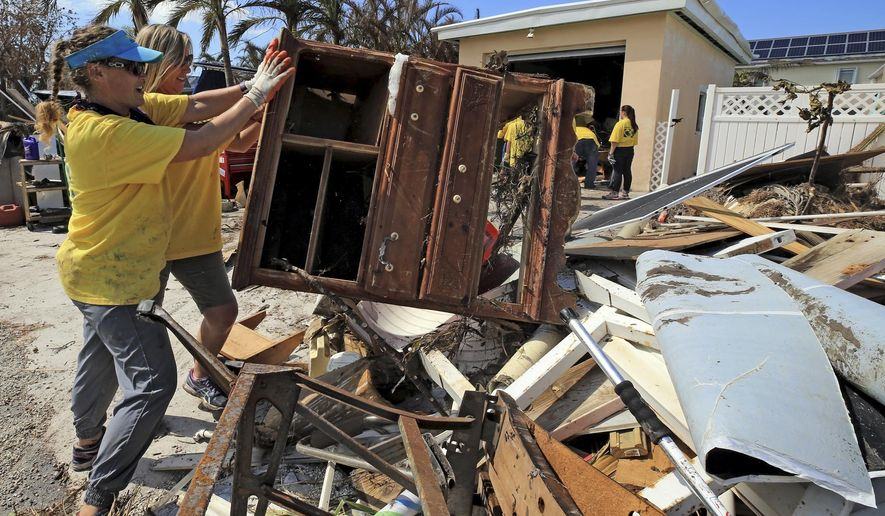 Maria Stotts, and Heather Mueller, volunteers from the Church of Jesus Christ of Latter-Day Saints, clear debris from a Monroe County sheriff's deputy's home damaged by a six-foot storm surge, Sunday, Sept. 17, 2017, in Big Pine Key, Fla. Residents were allowed to return to their homes in the Keys today a week after Hurricane Irma struck the Florida Keys (Al Diaz/Miami Herald via AP)