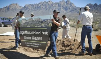 FILE - In this March 15, 2015 file photo, a sign is installed at the new Organ Mountain-Desert Peaks National Monument in Las Cruces, N.M. The boundaries of two national monuments in New Mexico that were part of an expansive federal review would remain unchanged under recommendations made by U.S. Interior Secretary Ryan Zinke, providing some relief to the groups that had come out in support of the designations. (Jett Loe/Las Cruces Sun-News via AP, File)