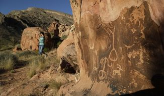 FILE - In this May 26, 2017, file photo, Susie Gelbart walks near petroglyphs at the Gold Butte National Monument near Bunkerville, Nev. nterior Secretary Ryan Zinke is recommending that four large national monuments in the West be reduced in size, potentially opening up hundreds of thousand or even millions of acres of land revered for natural beauty and historical significance to mining, logging and other development. Zinke's recommendation, revealed in a leaked memo submitted to the White House, prompted an outcry from environmental groups who promised to take the Trump administration to court to block the moves. (AP Photo/John Locher, File)