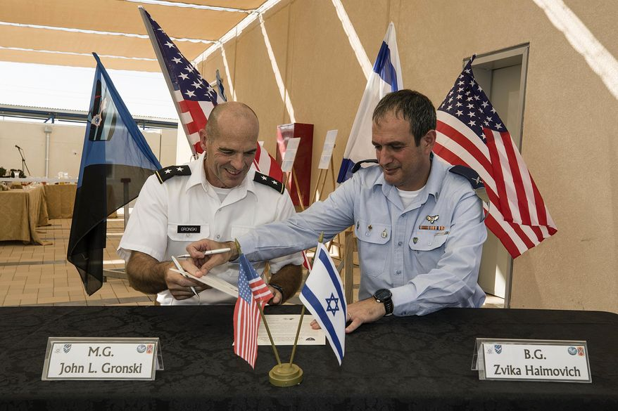 Israeli Defense Forces Brig. Gen. Zvika Haimovich, right, and U.S. Maj. Gen. John L. Gronski sign an agreement during a ceremony at the Bislach Air Base, near Mitzpe Ramon, Monday, Sept. 18, 2017. Israel and the United States announced plans Monday to open the first American air base in the Jewish state -- a facility that will aim to bolster Israel's aerial defenses. (AP Photo/Tsafrir Abayov)