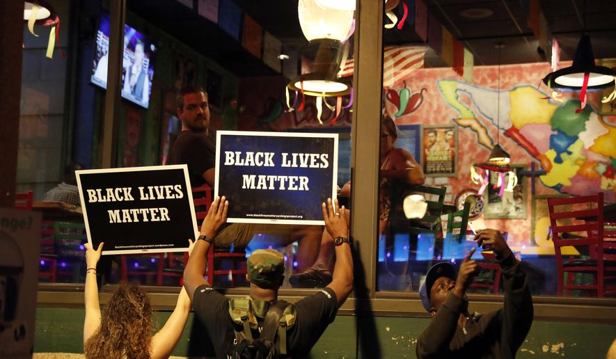 FILE - In this Sept. 15, 2017 file photo, protesters hold up signs as restaurant patrons look out the window in St. Louis. When a former police officer was acquitted in the fatal shooting of a black suspect, protesters vowed to show their disdain by disrupting business in downtown St. Louis. (AP Photo/Jeff Roberson, File)