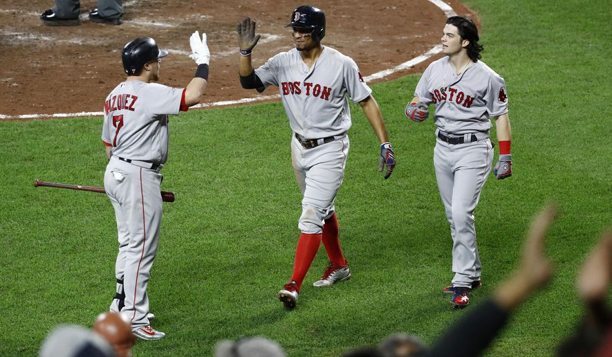 Boston Red Sox' Christian Vazquez, left, greets teammates Xander Bogaerts, center, and Andrew Benintendi after they scored on Mookie Betts' double in the fifth inning of a baseball game against the Baltimore Orioles in Baltimore, Monday, Sept. 18, 2017. (AP Photo/Patrick Semansky)