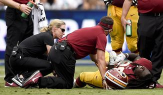 Washington Redskins' Rob Kelley (20) in tended to after being injured during the first half of an NFL football game against the Los Angele Rams Sunday, Sept. 17, 2017, in Los Angeles. (AP Photo/Kelvin Kuo)