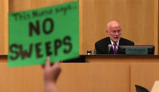A protester holds up a sign against Seattle City Council member Tim Burgess, right, who has been chosen by the Seattle City Council as temporary mayor, Monday, Sept. 18, 2017, at City Hall in Seattle. (Ken Lambert/TheSeattleTimesvia AP)