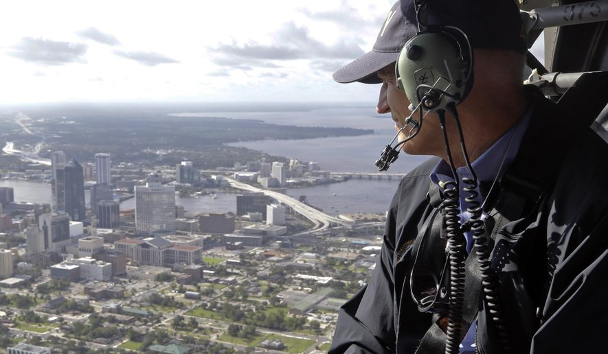 FILE - In this Sept. 12, 2017, file photo, Gov. Rick Scott assesses flooding damage over Jacksonville, Fla., in the aftermath of Hurricane Irma. The combined tab from Hurricanes Harvey and Irma is expected to hit $200 billion or more. While the federal government is expected to pay most of that, the affected state and local governments have to start paying for recovery now and eventually could be on the hook for tens of millions of dollars or more. (AP Photo/John Raoux, File)