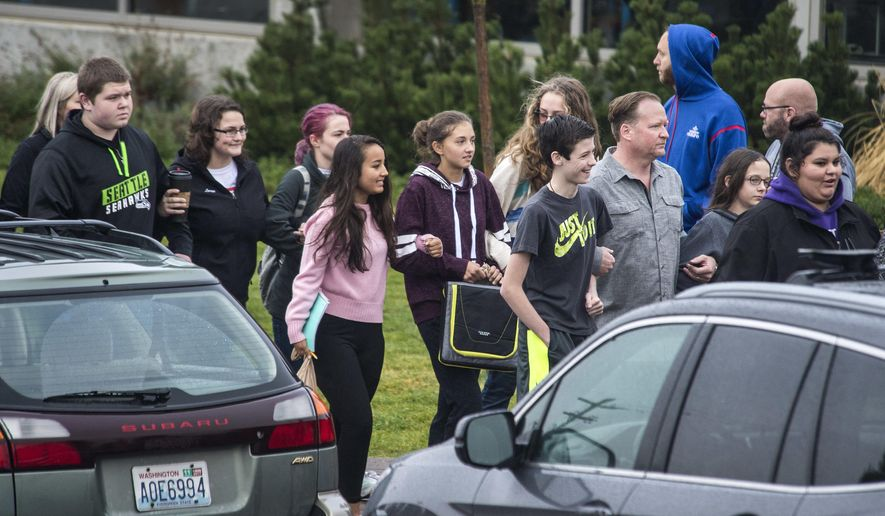 Freeman High School students walk arm-in-arm with parents, Monday, Sept. 18, 2017, near Rockford, Wash., as they re-enter the school to attend classes for the first time after a shooting left one student dead and three injured last week. (Dan Pelle/The Spokesman-Review via AP)
