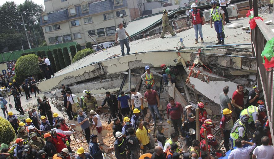 Rescue workers search for children trapped inside the collapsed Enrique Rebsamen school in Mexico City, Tuesday, Sept. 19, 2017. The earthquake stunned central Mexico, killing more than 100 people as buildings collapsed in plumes of dust. (AP Photo/Carlos Cisneros)