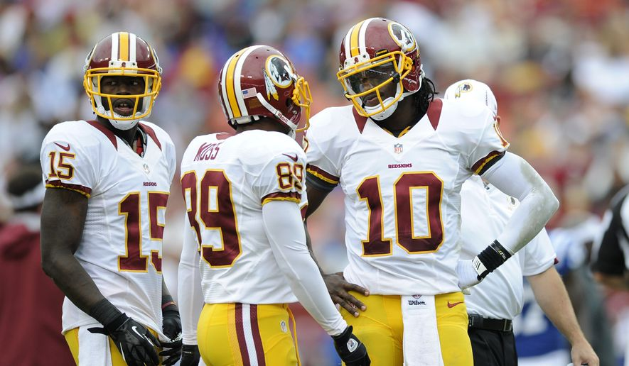 Washington Redskins quarterback Robert Griffin III (10) talks with teammates Santana Moss (89) and Josh Morgan (15) during a preseason NFL football game against the Indianapolis Colts, Saturday, Aug. 25, 2012, in Landover, Md. (AP Photo/Nick Wass)