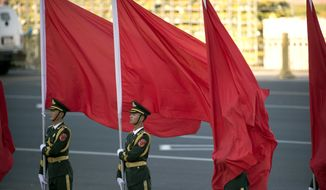 A Chinese honor guard member is caught in his flag as he stands at attention during a welcome ceremony for Singapore's Prime Minister Lee Hsien Loong at the Great Hall of the People in Beijing, Tuesday, Sept. 19, 2017. (AP Photo/Mark Schiefelbein)