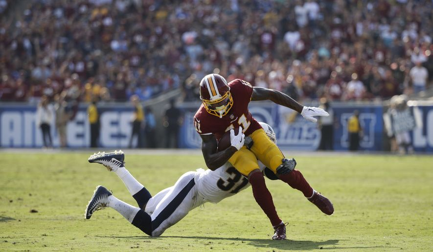 Washington Redskins' Terrelle Pryor is stopped by Los Angeles Rams' Maurice Alexander the ball during an NFL football game Sunday, Sept. 17, 2017, in Los Angeles. (AP Photo/Jae C. Hong)