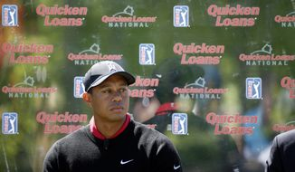 FILE - In this May 16, 2016, file photo, Tiger Woods pauses during a Quicken Loans National golf tournament media availability on the 10th tee at Congressional Country Club in Bethesda, Md. The tournament that Woods launched 10 years ago remained on next season's PGA Tour schedule. Still to be determined is where,  and if, it is held. The tour has opted out of its contract with Congressional next year as it tries to find a title sponsor. (AP Photo/Alex Brandon, File) **FILE**