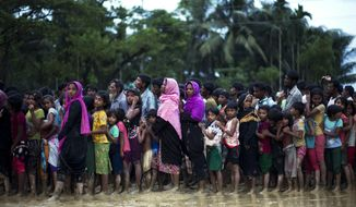 Rohingya Muslims, who crossed over recently from Myanmar into Bangladesh, stand in a queue to receive food being distributed near Balukhali refugee camp in Cox's Bazar, Bangladesh, Tuesday, Sept. 19, 2017. More than 500,000 Rohingya Muslims have fled to neighboring Bangladesh in the past year, most of them in the last three weeks, after security forces and allied mobs retaliated  to a series of attacks by Muslim militants last month by burning down thousands of Rohingya homes in the predominantly Buddhist nation. (AP Photo/Bernat Armangue)