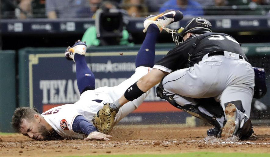 Houston Astros' George Springer, left, touches home plate to score as Chicago White Sox catcher Kevan Smith reaches to tag him during the eighth inning of a baseball game Tuesday, Sept. 19, 2017, in Houston. (AP Photo/David J. Phillip)