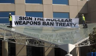 Two anti-nuclear weapons campaigners Gem Romuld, left, and Papatya Danis unfurl a banner at the Department of Foreign Affairs and Trade building in Canberra Wednesday, Sept. 20, 2017, to protest the government's failure to endorse a United Nations' nuclear disarmament treaty. (AP Photo/Rod McGuirk)
