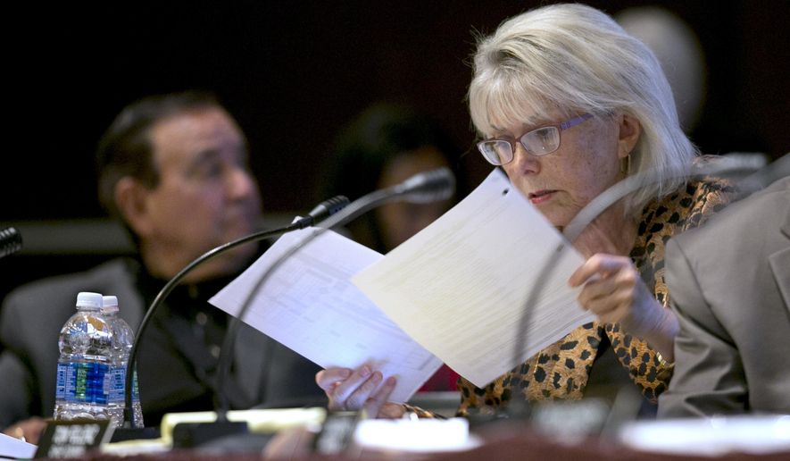 Lynn Schenk, a member of the California High-Speed Rail Authority, looks over papers at a rail board hearing Tuesday, Sept. 19, 2017, in Sacramento, Calif. Schenk and fellow board member Ernest Camacho, left, were critical of the budget overruns in the construction of the first leg of the rail system. (AP Photo/Rich Pedroncelli)
