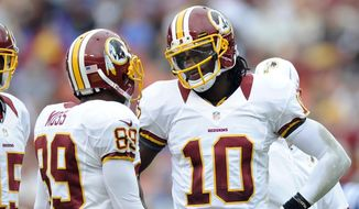 In this Aug. 25, 2012, file photo, Washington Redskins quarterback Robert Griffin III (10) talks with teammates Santana Moss (89)) during a preseason NFL football game against the Indianapolis Colts in Landover, Md. (AP Photo/Nick Wass, File)