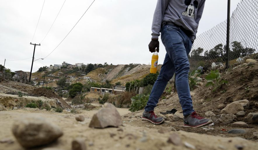 In this May 24, 2017 photo, a Haitian man makes his way up a dirt road towards a makeshift shelter at The Ambassadors of Jesus Church in Tijuana, Mexico. He is among about 4,000 Haitians to establish roots in Mexico's northwest corner after the United States abruptly closed its doors late last year. The Mexican government has welcomed them, and they are already having an outsize economic and cultural impact. (AP Photo/Gregory Bull)