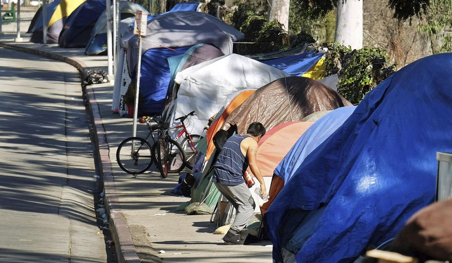 FILE - This Tuesday, Jan. 26, 2016 file photo shows a homeless encampment on a street in downtown Los Angeles. Public health authorities on Tuesday, Sept. 19, 2017, declared an outbreak of the highly contagious liver disease hepatitis A in Los Angeles County, the third California region to see significant infections this year. Health officials reported the outbreak to the county Board of Supervisors, which requested a briefing due to the proximity of LA to San Diego, which has had more than 420 cases and more than a dozen deaths since early this year. (AP Photo/Richard Vogel, File)