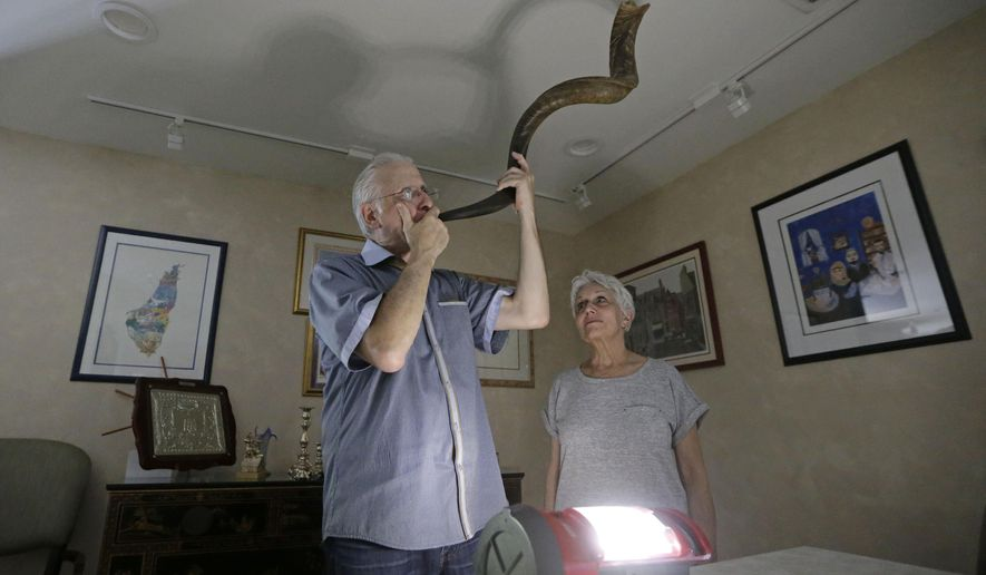 "Michael Andron blows the shofar as he prepares for Rosh Hashanah, as his wife Lillian watches as they use a battery powered lantern to illuminate the room at their home, Tuesday, Sept.19, 2017, in Miami. The Androns have been without power for nine days due to Hurricane Irma, I feel like this year Rosh Hashanah became even more important because we just want to get in touch with the Infinite, so I feel like I don't need to do the big meal and have company. This year I just wanted to be more reflective and listen to my husband blow the shofar,"" said Lillian Andron during an interview. (AP Photo/Alan Diaz)"