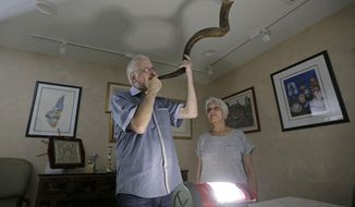 """Michael Andron blows the shofar as he prepares for Rosh Hashanah, as his wife Lillian watches as they use a battery powered lantern to illuminate the room at their home, Tuesday, Sept.19, 2017, in Miami. The Androns have been without power for nine days due to Hurricane Irma, I feel like this year Rosh Hashanah became even more important because we just want to get in touch with the Infinite, so I feel like I don't need to do the big meal and have company. This year I just wanted to be more reflective and listen to my husband blow the shofar,"""" said Lillian Andron during an interview. (AP Photo/Alan Diaz)"""