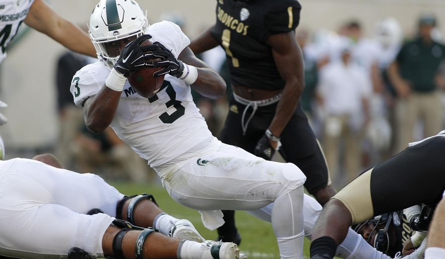 FILE - In this Saturday, Sept. 9, 2017, file photo, Michigan State running back LJ Scott (3) stretches over the goal line for a touchdown against Western Michigan during the fourth quarter of an NCAA college football game in East Lansing, Mich. Michigan State has run the ball effectively through two games, and the scary thing for Notre Dame, this week's opponent, is that Scott hasn't even gotten going yet. (AP Photo/Al Goldis, File)