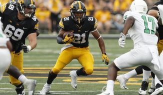 Iowa running back Ivory Kelly-Martin (21) runs from North Texas linebacker Joe Ozougwu, right, during the second half of an NCAA college football game, Saturday, Sept. 16, 2017, in Iowa City, Iowa. (AP Photo/Charlie Neibergall)