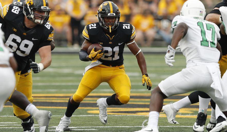 Iowa running back Ivory Kelly-Martin (21) runs from North Texas linebacker Joe Ozougwu, right, during the second half of an NCAA college football game, Saturday, Sept. 16, 2017, in Iowa City, Iowa. (AP Photo/Charlie Neibergall)