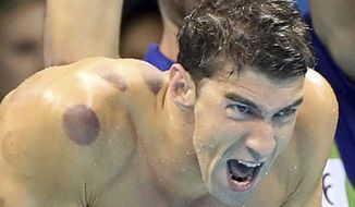 "FILE - In this Aug. 7, 2016, file photo United States swimmer Michael Phelps encourages his teammates in the final of the men's 4x100-meter freestyle relay during the swimming competitions at the 2016 Summer Olympics in Rio de Janeiro, Brazil. Phelps says he has ""no desire"" to return to competitive swimming, but he's eager to stay involved with the sport and cheer on those who follow in his enormous wake.  (AP Photo/Lee Jin-man, File)"