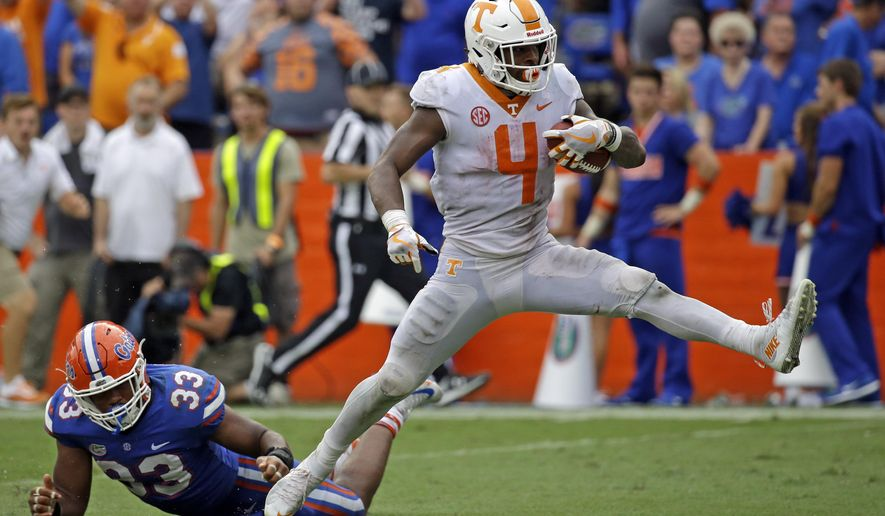 Tennessee running back John Kelly (4) scores a touchdown past Florida linebacker David Reese (33) on a 34-yard run in the second half of an NCAA college football game, Saturday, Sept. 16, 2017, in Gainesville, Fla. Florida won 26-20. (AP Photo/John Raoux)