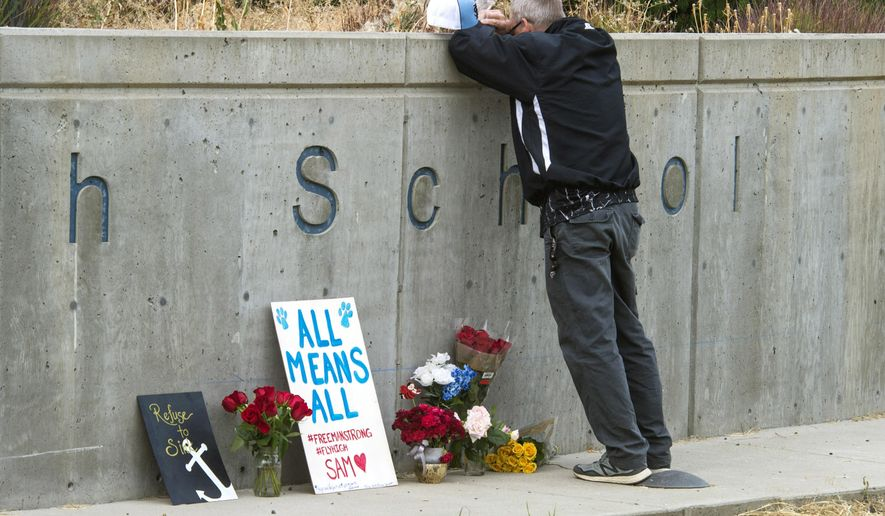FILE - In this Sept. 14, 2017 file photo, Freeman High School assistant football coach Tim Smetana grieves after he placed roses at a memorial to the shooting victims at the school in Rockford, Wash. Students returned Monday, Sept. 18, 2017 to the school south of Spokane, Wash., for the first time since last Wednesday's shootings that left one student dead and three wounded. (Dan Pelle/The Spokesman-Review via AP, File)