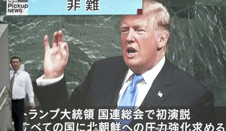 A man walks past a TV screen showing U.S. President Donald Trump speaks at the U.N. General Assembly, in Tokyo Wednesday, Sept. 20, 2017. Trump's threat before the world to obliterate North Korea left no doubt about his determination to stop the communist country's nuclear weapons buildup. (AP Photo/Eugene Hoshiko)