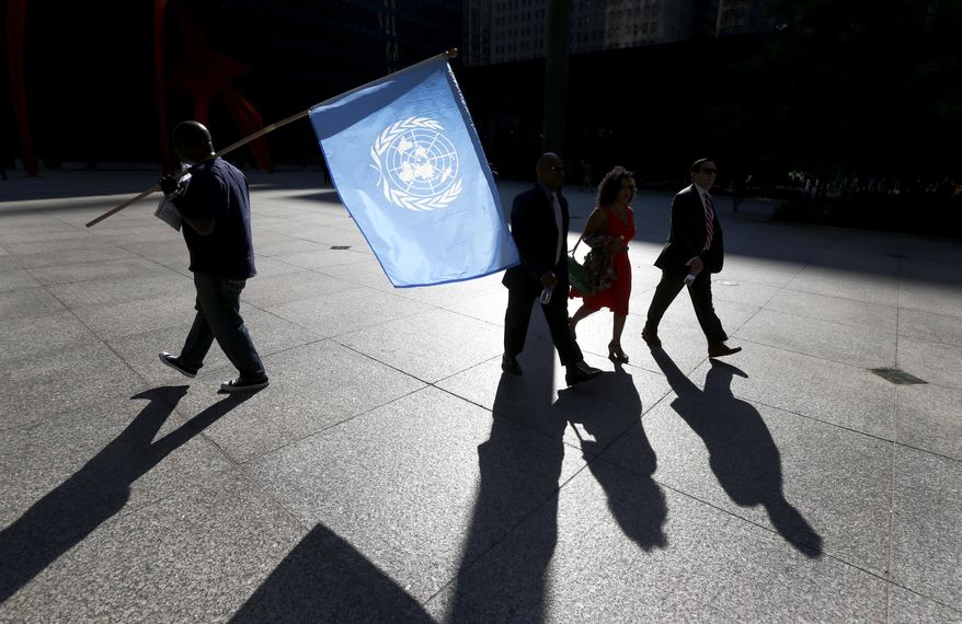 A protester is silhouetted as he carries the United Nations flag during a rally against Nigerian President Buhari as pedestrians walk through federal plaza Wednesday, Sept. 20, 2017, in Chicago. (AP Photo/Charles Rex Arbogast)