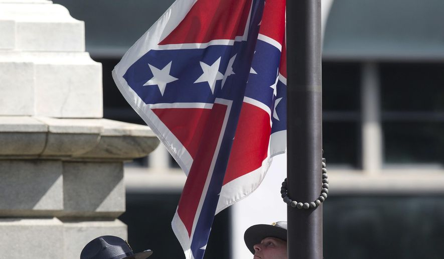 In this July 10, 2015 file photo, an honor guard from the South Carolina Highway patrol removes the Confederate battle flag from the Capitol grounds in Columbia, S.C., ending its 54-year presence there. (AP Photo/John Bazemore, File) **FILE**