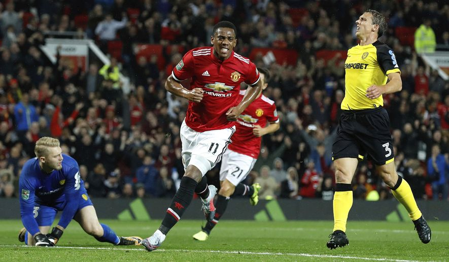 Manchester United's Anthony Martial celebrates scoring his side's fourth goal of the game against Burton Albion, during their English League Cup soccer match at Old Trafford in Manchester, England, Wednesday Sept. 20, 2017. (Martin Rickett/PA via AP)