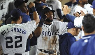 San Diego Padres' Manuel Margot is congratulated in the dugout after scoring on a RBI single by Carlos Asuaje during the sixth inning of a baseball against the Arizona Diamondbacks game Tuesday, Sept. 19, 2017, in San Diego. (AP Photo/Orlando Ramirez)