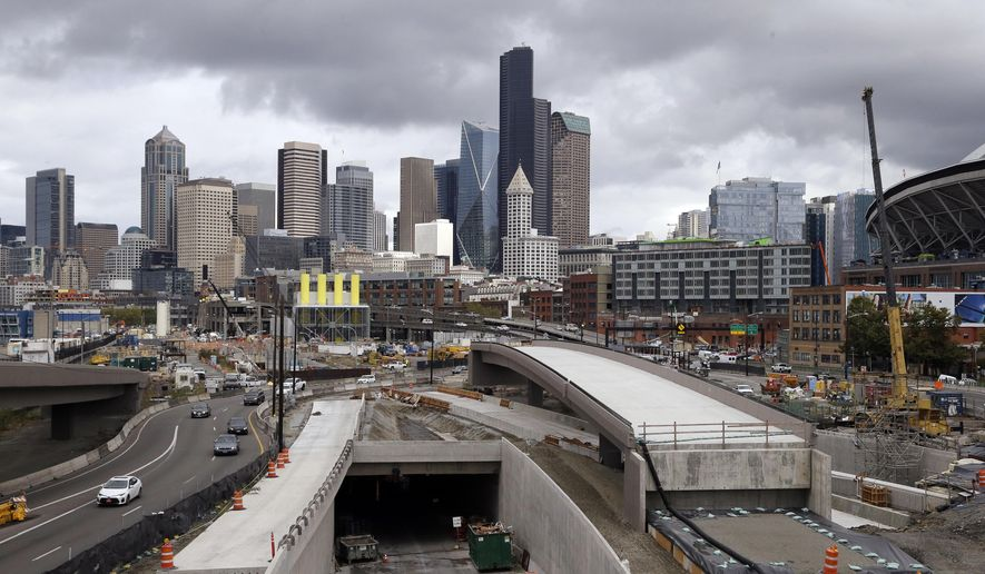 In this file photo taken Tuesday, Sept. 19, 2017, a portion of a new offramp, center right, for Highway 99, stands completed and adjacent to the entrance for northbound traffic into the Highway 99 tunnel still being constructed in Seattle. The offramp has a new type of column that flexes when the ground shakes in an earthquake, then snaps back to its original position so that the structure not only survives a quake without collapsing but also sustains so little damage that it can be used immediately. (AP Photo/Elaine Thompson) ** FILE **