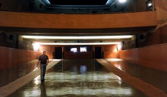 In this Thursday, Sept. 14, 2017 photo, Rhyne Hobbs, the general manager of Eastland's Majestic Theatre, walks across the glossy floor of the now-empty auditorium in Eastland, Texas, while describing the new seats to be installed this week in the historic theater. The 70 year-old seats we be replaced by modern, padded chairs that feature cup-holders and can recline slightly. (Ronald W. Erdrich/The Abilene Reporter-News via AP)
