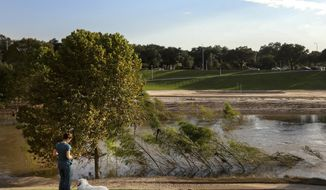 Taylor Pence walks her dog at Buffalo Bayou Park, Tuesday, Sept. 12, 2017, in Houston. Runners and bikers returning to the park in the wake of Hurricane Harvey are finding a vastly different landscape, more desert than prairie, blanketed with untold tons of sandy sediment.   (Jon Shapley/Houston Chronicle via AP)